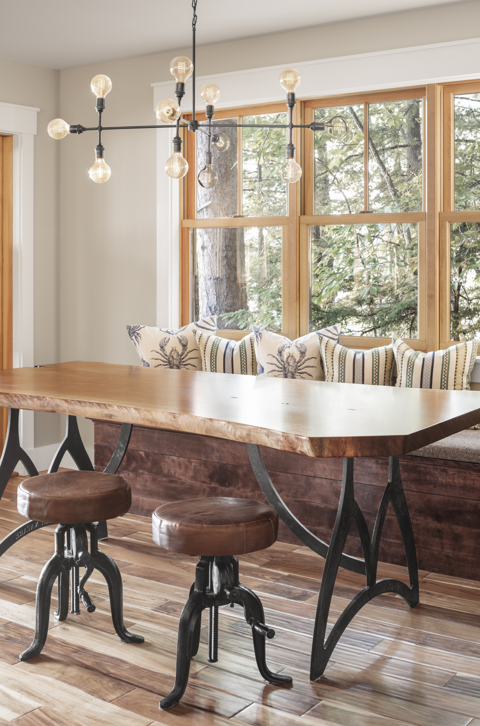 This live edge black walnut dining table was designed by Vanessa Helmick and built in Gorham by Tim Hill fine woodworking. The base has a latin inscription cut into the steel. A solid slab of wood is MEANT TO BE USED-scratched, weather. Perfect for a growing family and a summer house full of guests! The banquette seating is designed for storage-it holds cots that can be taken out to sleep cousins and friends! Cushions and pillows are indoor outdoor fabric, perfect for lake living in Maine.