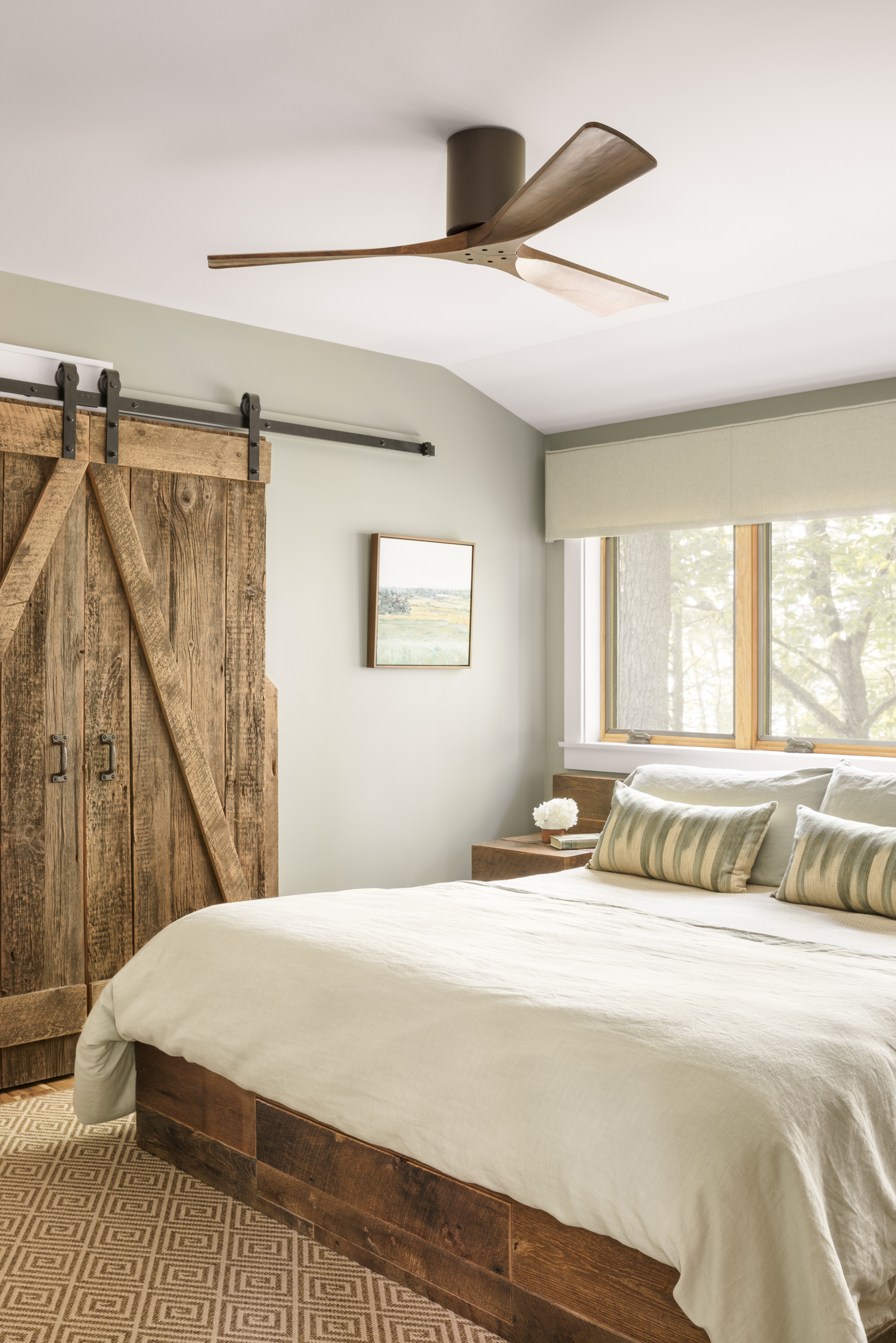 This master bedroom has an indoor outdoor rug that looks like natural fiber-but it can be hosed off and will last for decades! The custom bed has 5 hidden drawers in it, eliminating the need for a dresser. Built out of reclaimed wood from Maine. The window covering conceals a motorized blackout shade-very helpful for Maine summers where the sun rises before 6am!