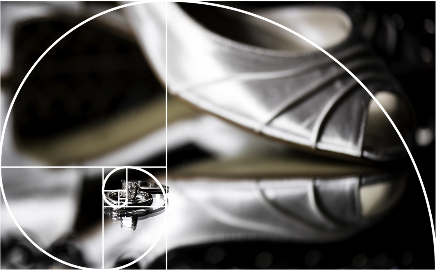 An overlay of the Golden Ratio over a shot of an engagement ring and wedding band