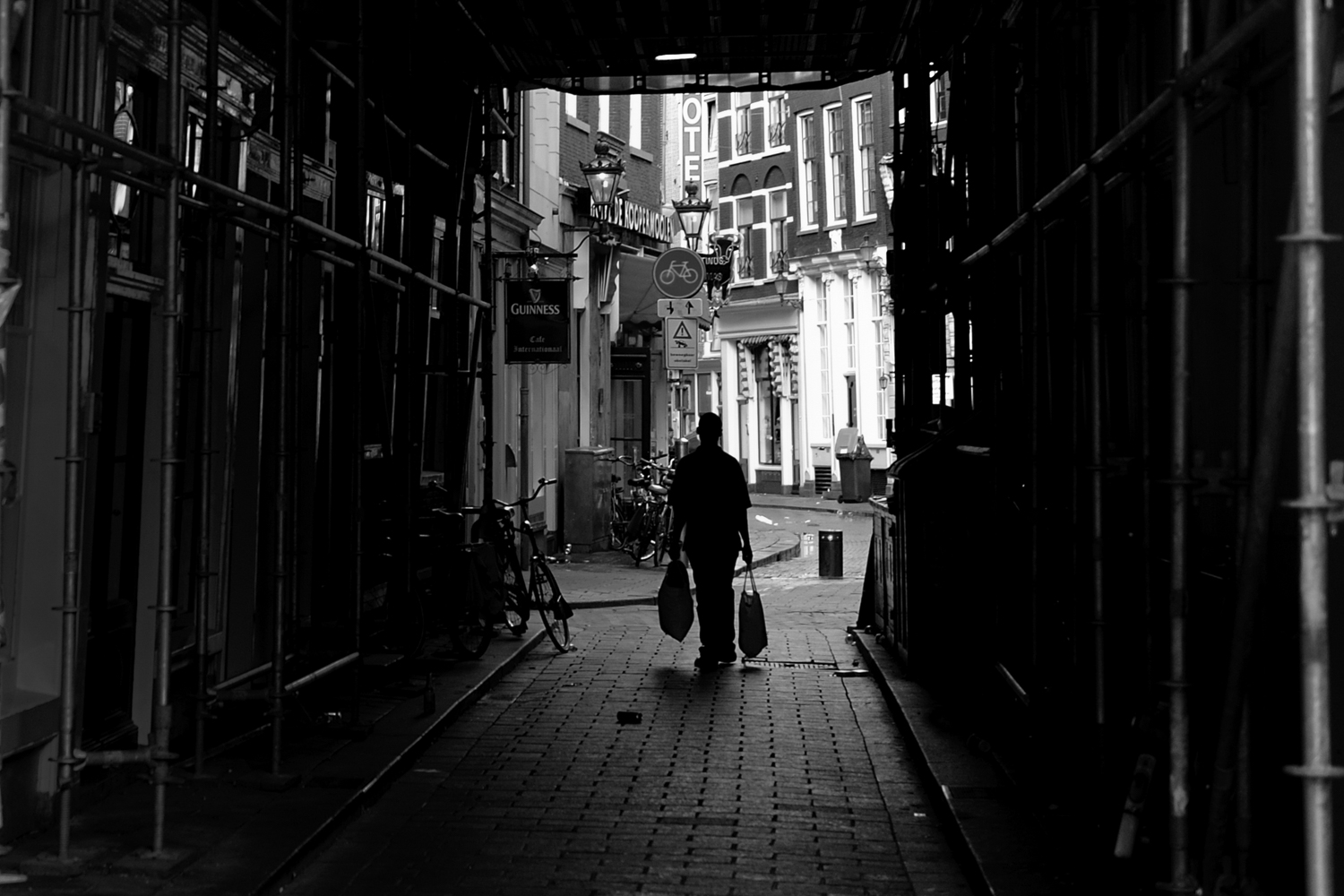 A man walking through an alley with bags