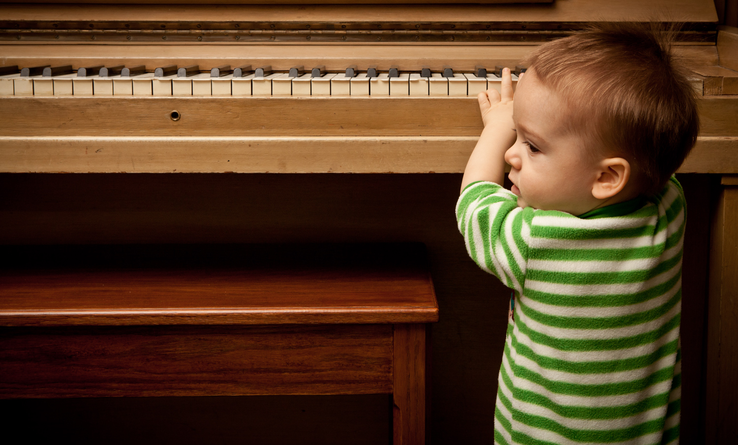 A little boy playing the piano.