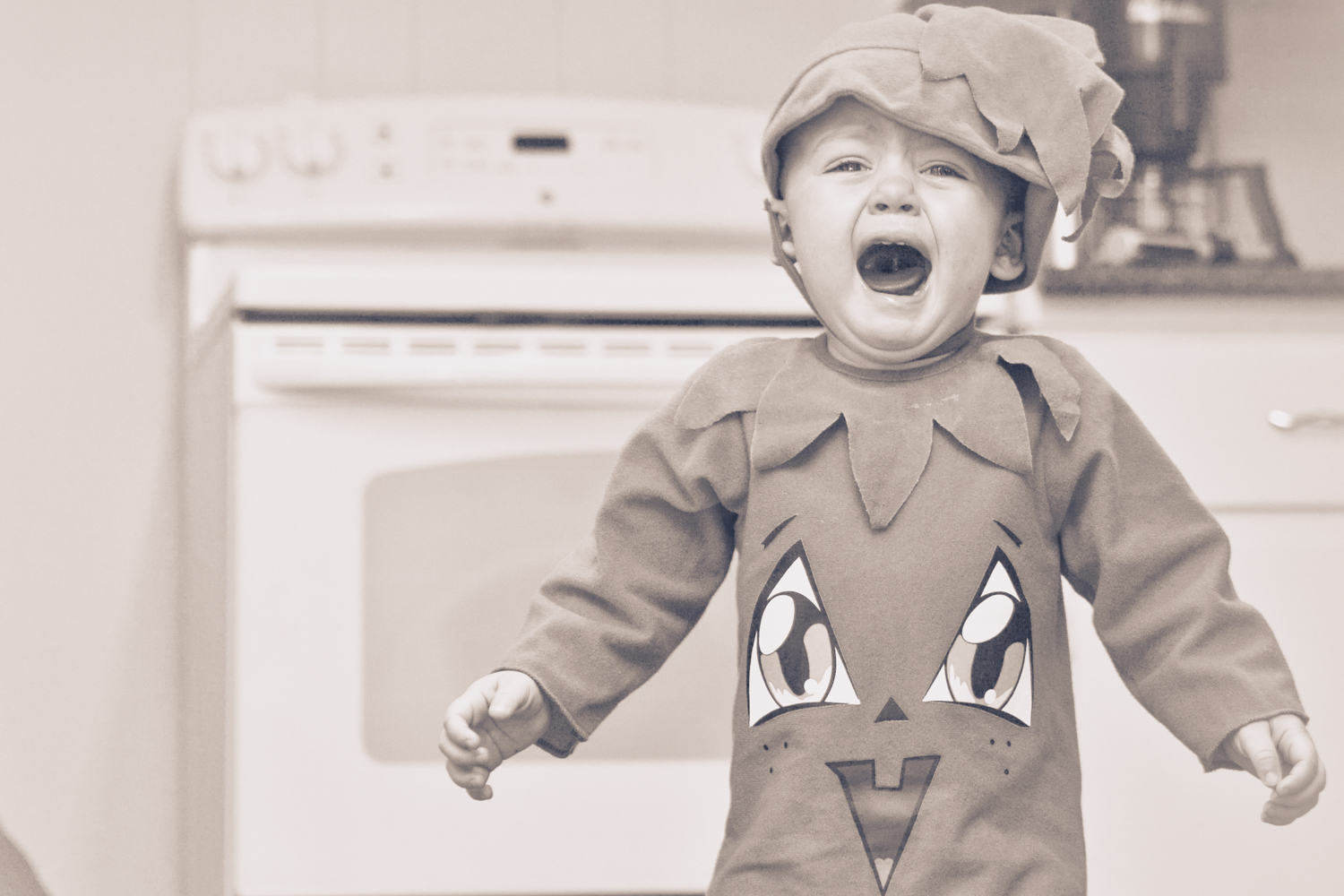A little boy in a costume crying.