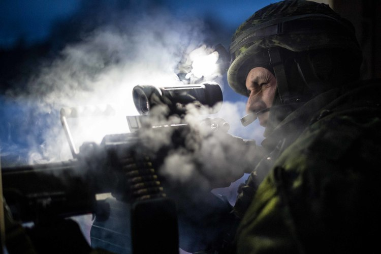 A Canadian Forces member looking through his machine gun scope.
