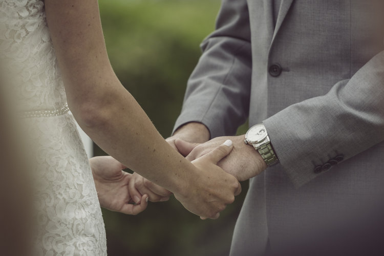 Laura and Billy holding hands during their wedding vows.