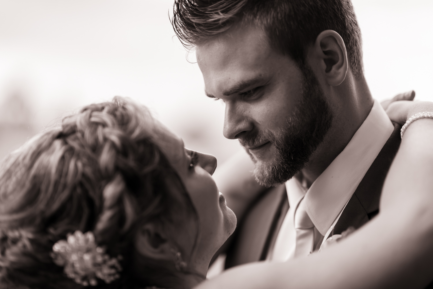 The bride and groom looking into one anothers' eyes during their first dance as newlyweds.