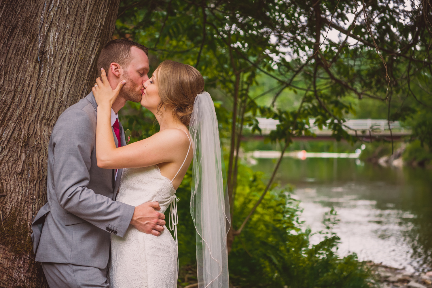 A quiet kiss and a peaceful start to a new life between a bride and groom in a moment by the water.