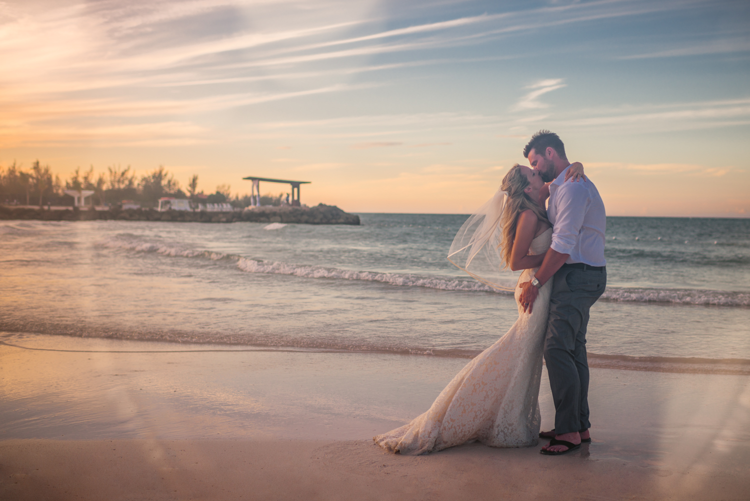 Laura and Allan, the bride and groom, kiss after their destination wedding on the beach in Montego Bay, Jamaica.