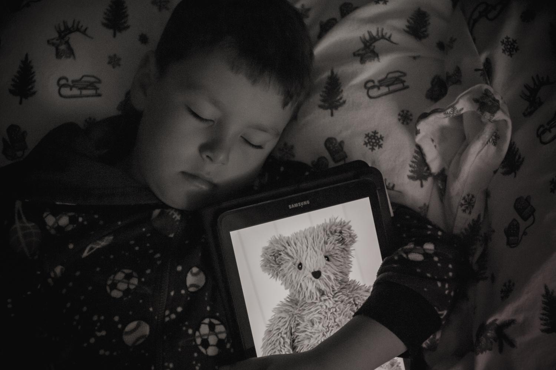 Luke with a teddy bear on a tablet