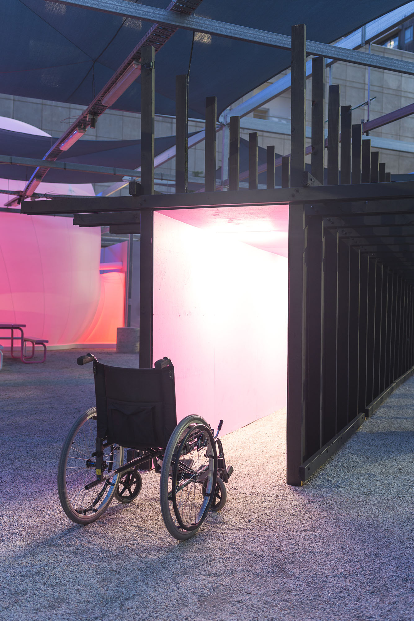 Hostile Infrastructure , install view.  Manual wheelchair, marine plywood, structural pine, exterior acrylic paint, LED lights, LTECH decoder  18m x 3m x 3m  2019   An empty wheelchair sits outside at night in front of a corridor lit from within and painted pink. The skeleton of the corridor is exposed and painted black