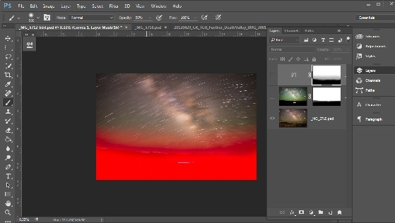 This screenshot from Photoshop shows the two layers, and the mask used to block the bottom of the top layer (the dark sky) to allow the bottom of the bottom layer (the landscape) to come through.