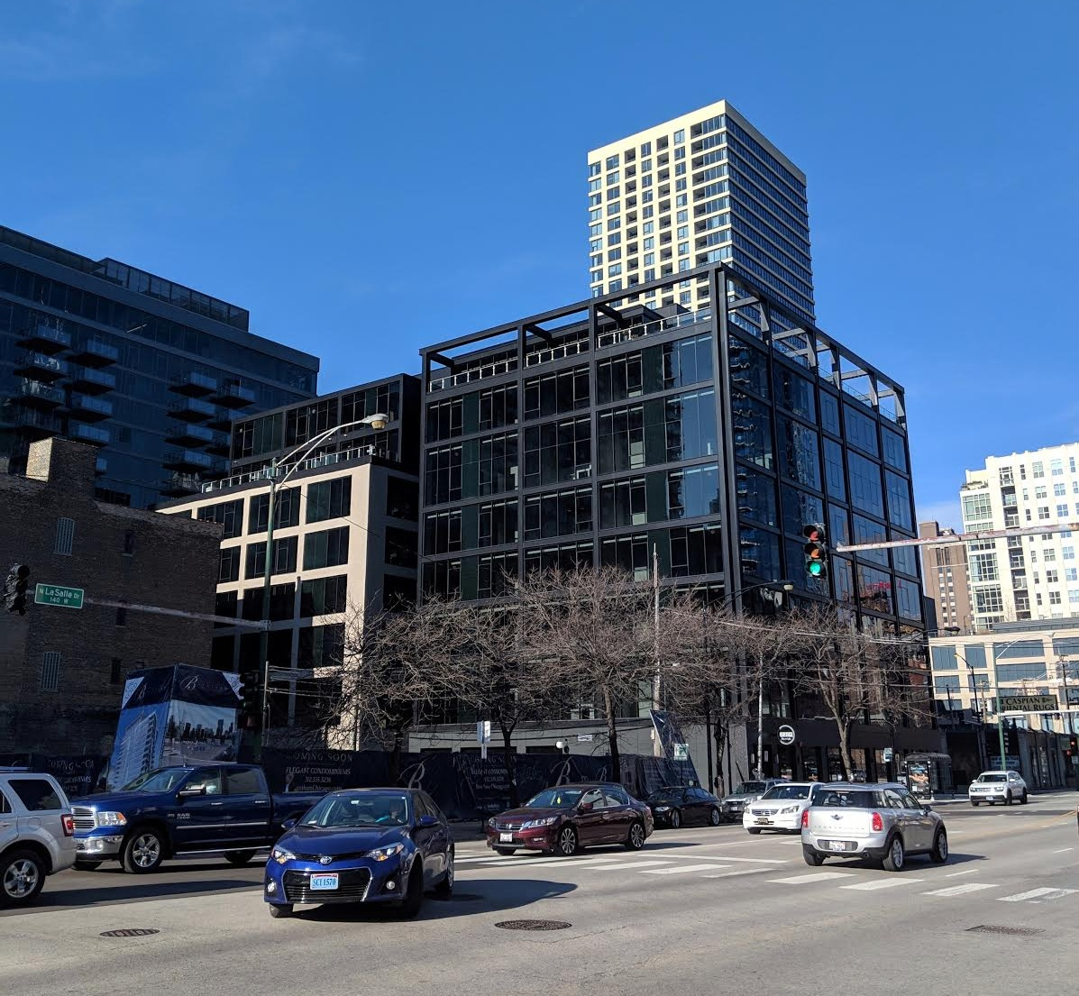 The existing building is in beige on the left and the new building is in black steel and glass on the right. Photo: George Guarino