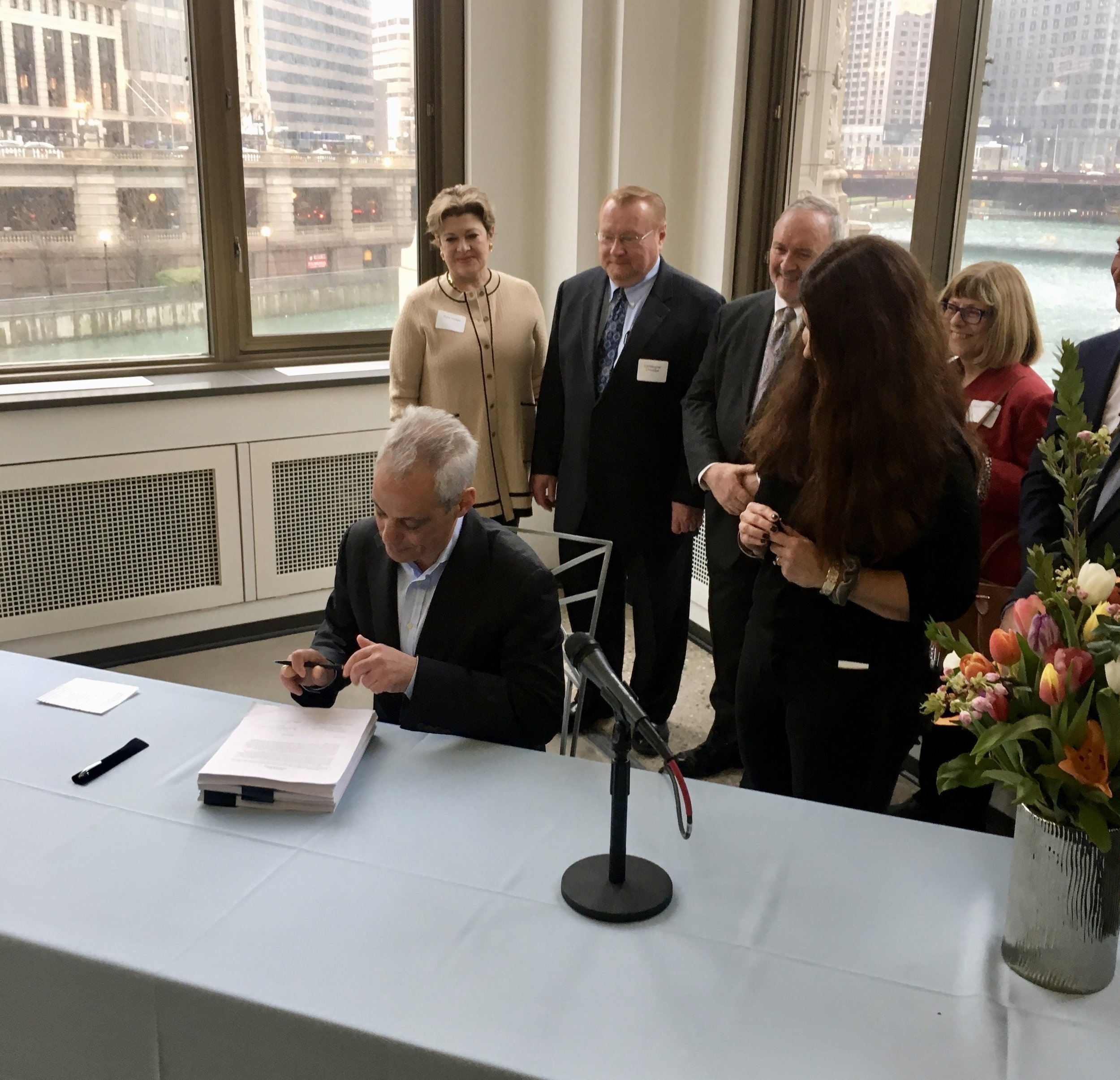 Commissioner Judy Frydland overlooks Mayor Rahm Emanuel ceremoniously signs the updated building code legislation. Photo by Steven Vance