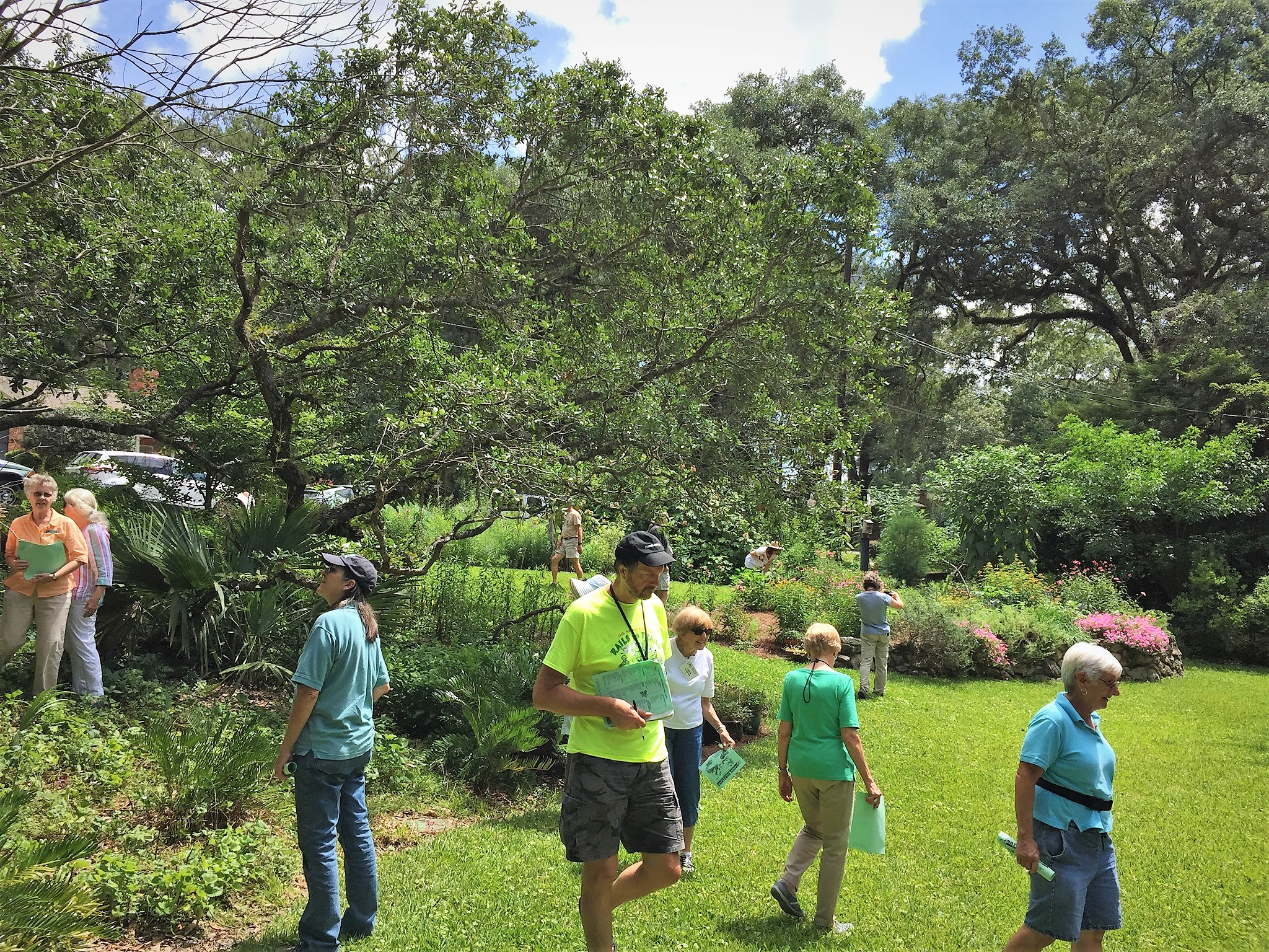 Florida Native Plant Society members examine the large mulched and planted beds that slow down the flow of rainwater in Legare's front yard. Photo by Jody Walthall.