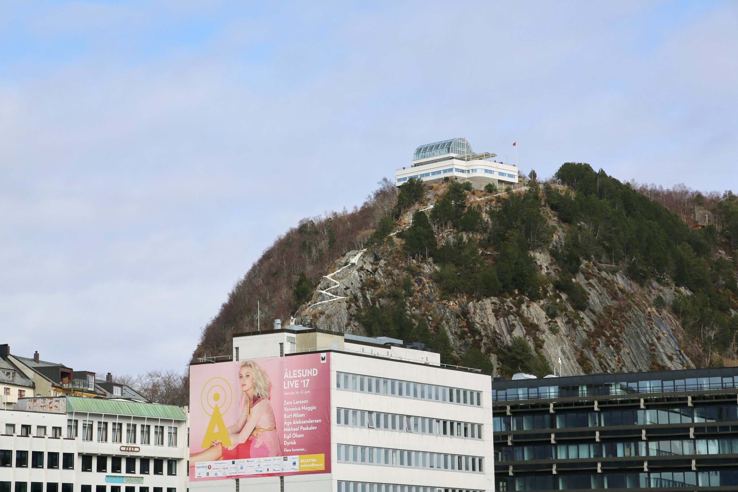 Den hvite stien midt i bildet i fjellsiden fører deg 140 meter opp i fra havet. Foto: Odd Roar Lange