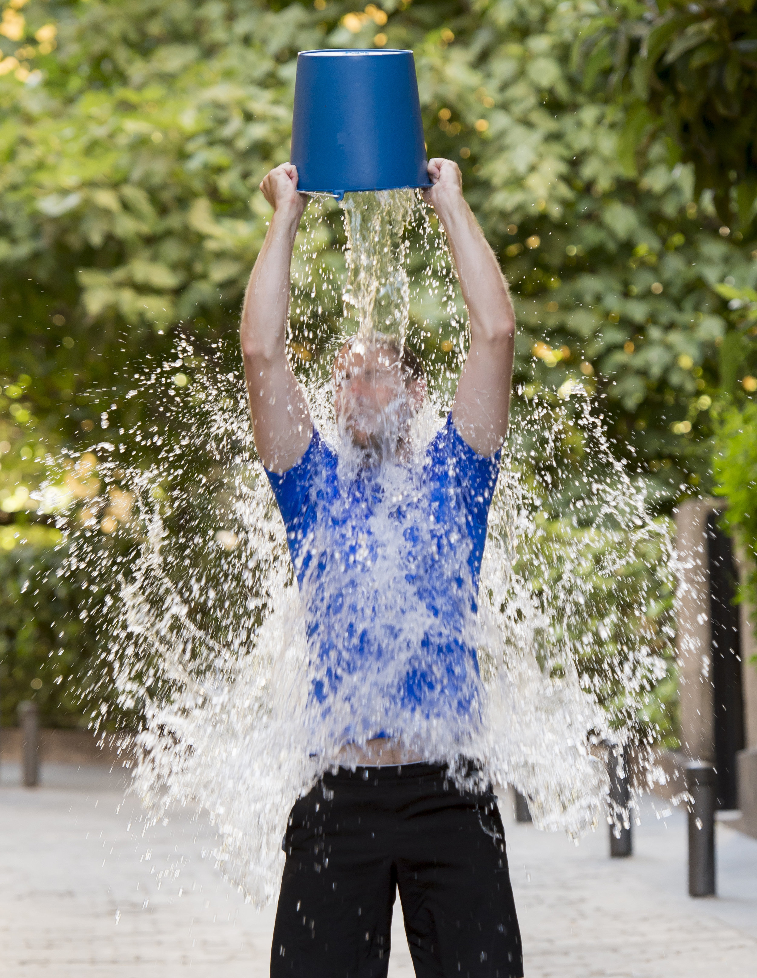 young man pouring ice water bucket on his head getting wet outdoors in internet viral media network challenge campaign to support degenerati.jpg