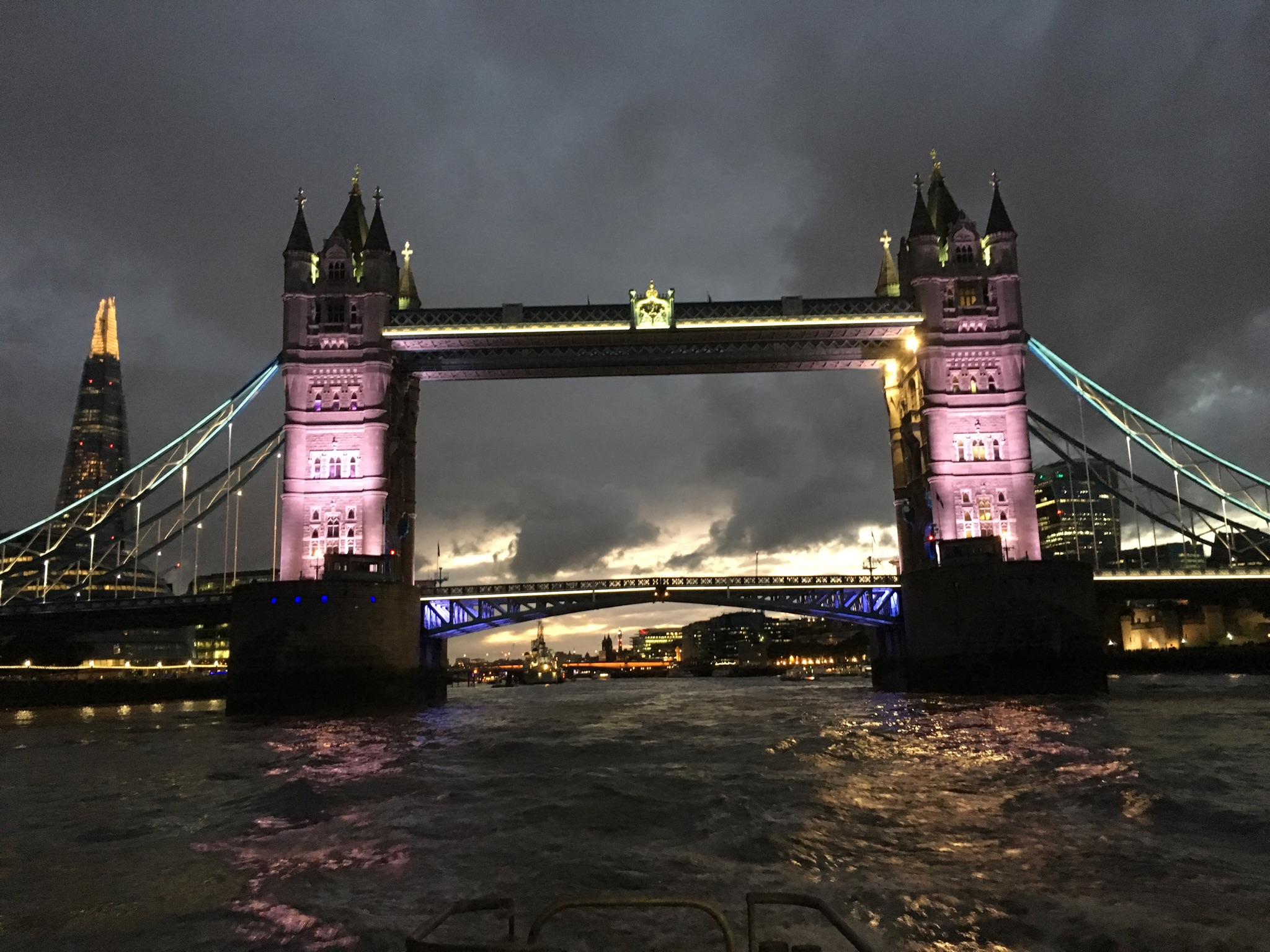 Tower Bridge at night while on the River Thames.