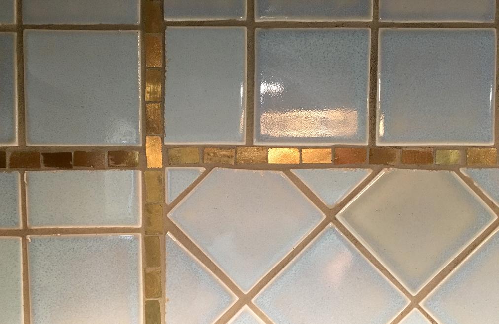 Simple custom 24k gold mosaic backsplash border design.