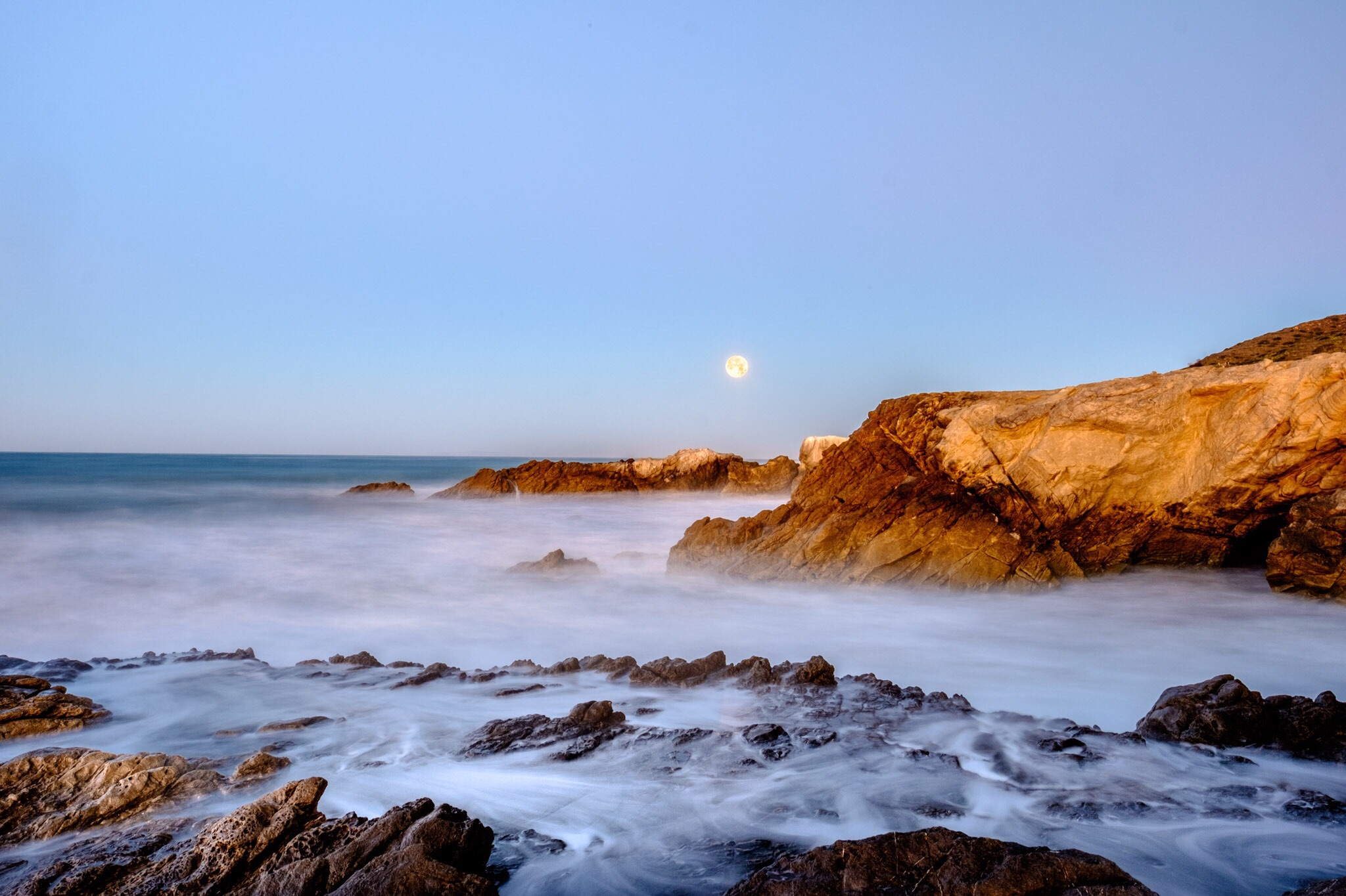 "The California Coast and the setting moon during ""blue hour."""