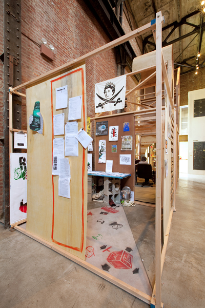 House Magic: Bureau of Foreign Correspondence Working Research Office ,  University of Trash , 2009, 96 x 96 x 96 in. wood, printed material, and videos. Produced by Alan Moore and the ABC No Rio Visual Arts collective. Photo: Jason Mandella