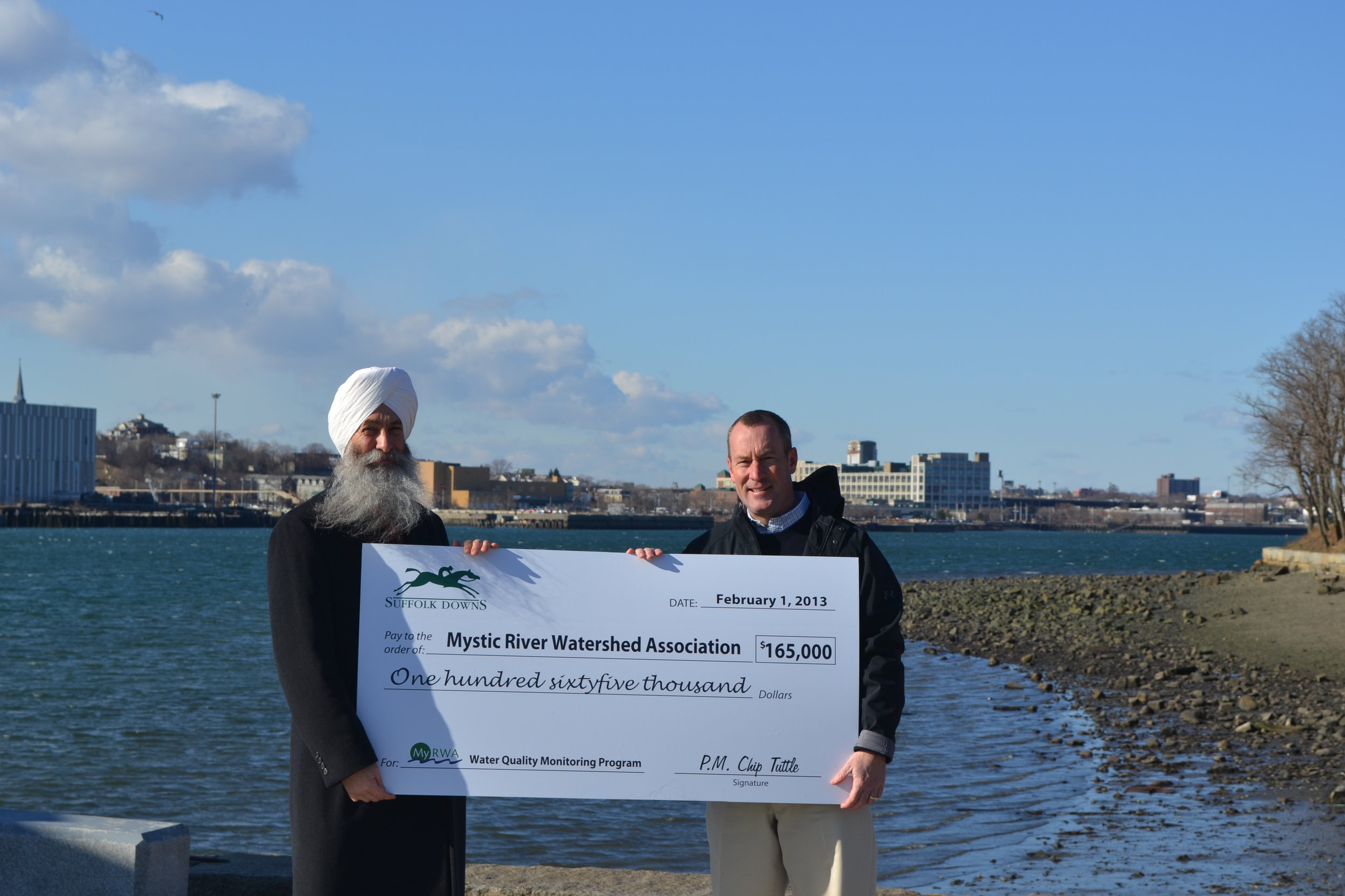 EkOngKar Singh Khalsa, Executive Director - Mystic River Watershed Association and Chip Tuttle, Chief Operating Officer - Suffolk Downs, celebrate Suffolk Downs' support of local water quality monitoring and improvement efforts. (Pictured above on the banks of the Mystic River at Mary O'Malley Park in Chelsea.