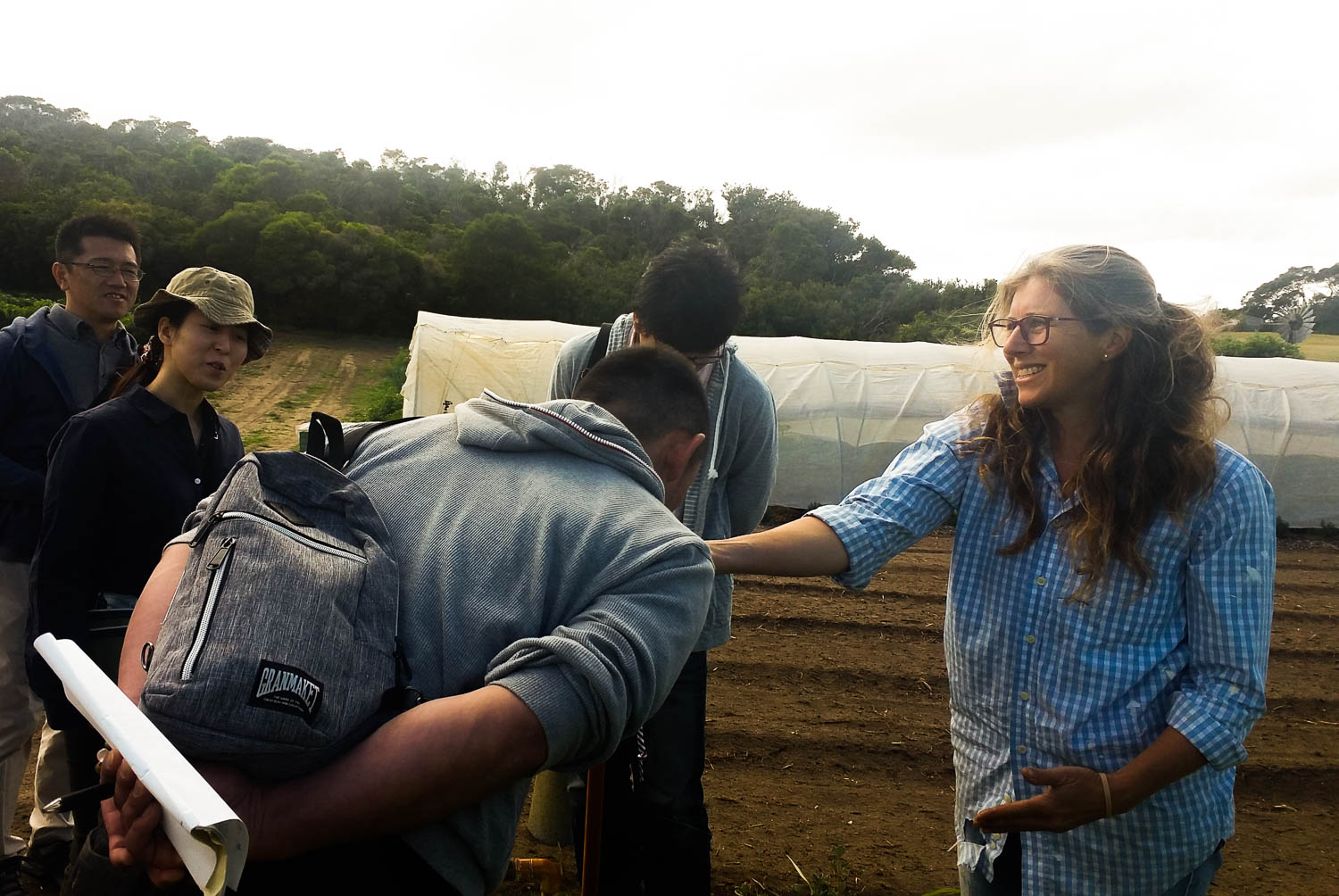Language barriers are overcome as Robin gives a group of Japanese farmers interested in organic farming techniques a handful of soil to smell, taste and touch.
