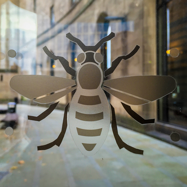 Modern-day bee on Library Walk Passage glass panel.