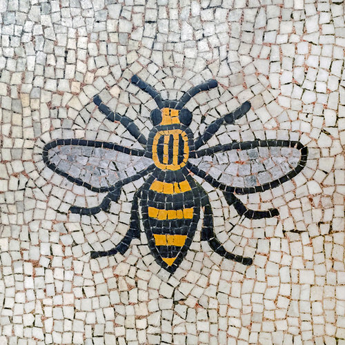All Across The City - In modern day Manchester the bees have broken out of the confines of the heraldic arms and have been incorporated into creative renderings of business logos and graffiti art. Within Manchester's magnificent Town Hall, a splendid bee mosaic tiled floor adorns the landing leading to the building's Great Hall. The recently installed £3.5m glass passageway across Library Walk, linking Central Library to the town hall extension, has bee motifs on its glass panels.