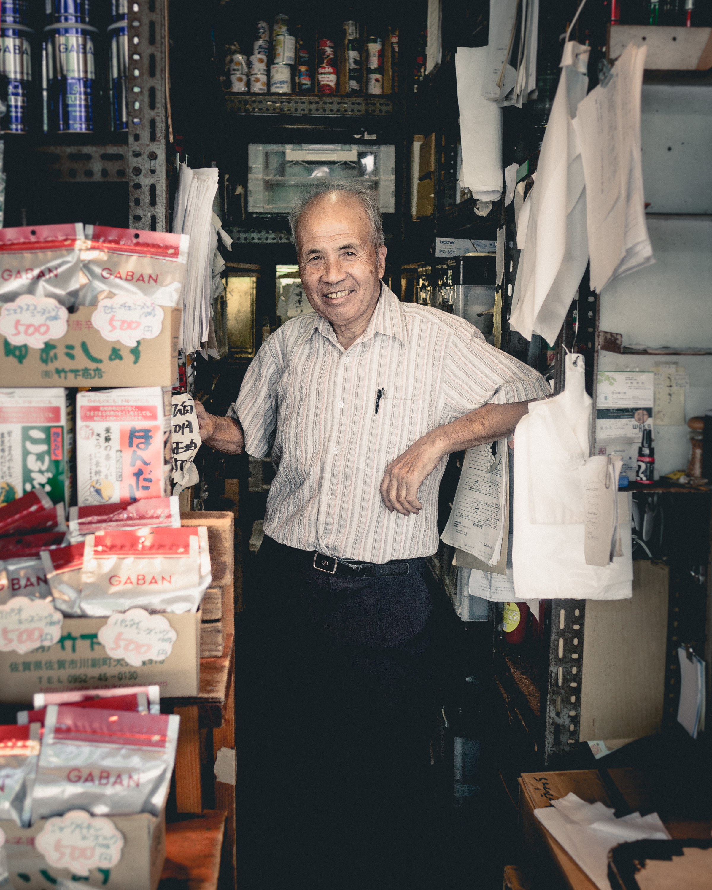 Street Photography Shot of An elderly vendor manning his shop in Tsukiji fish market, Tokyo, Japan. He very kindly takes a moment to pose for a photo.