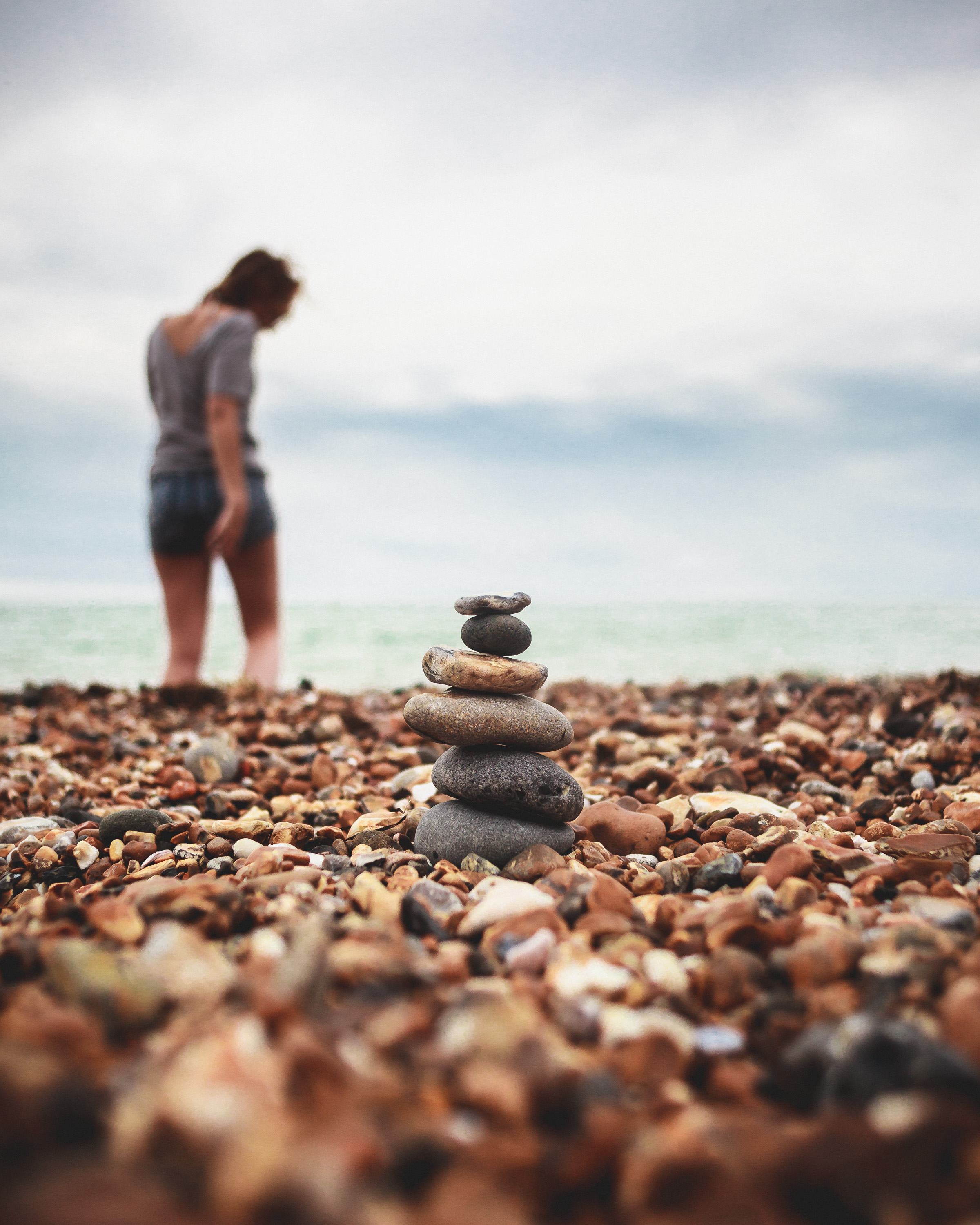 Zen stone tower built of pebbles on the beach with girl walking into the see in the distance