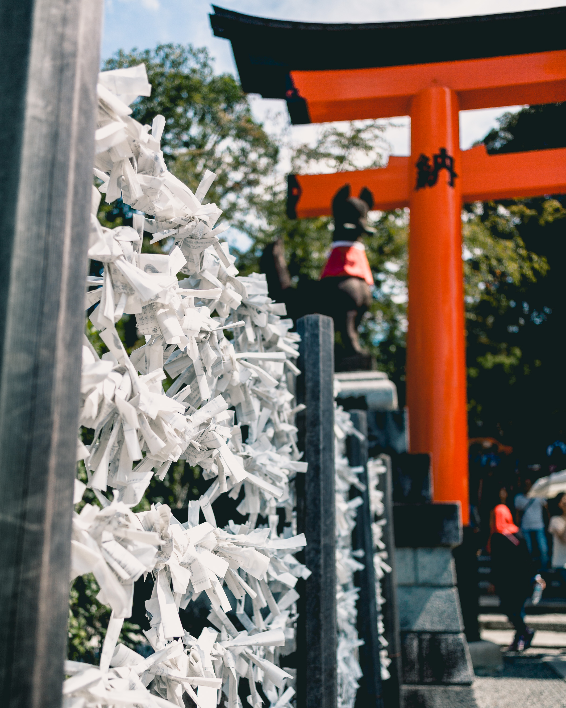 Paper Fortunes tied to a fence below a giant orange Torii Gate at Fushimi Inari Shrine, Kyoto, Japan