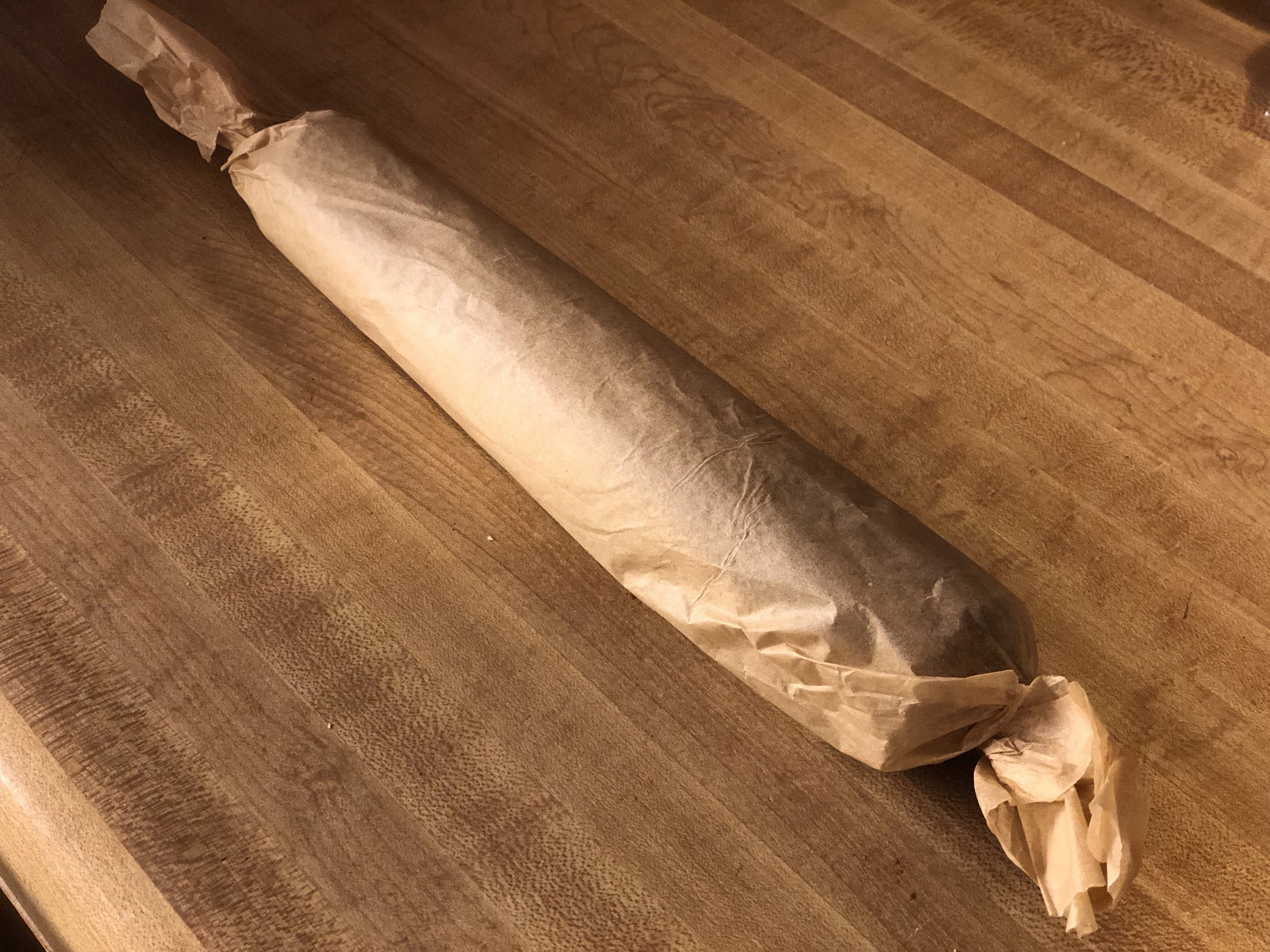 Roll the coconut log tightly with parchment paper and twist the ends. Place in the freezer 20-45min
