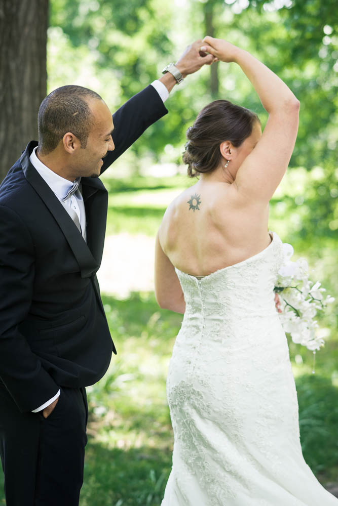 A portrait of a bride and groom during their first look in Tower Grove Park.