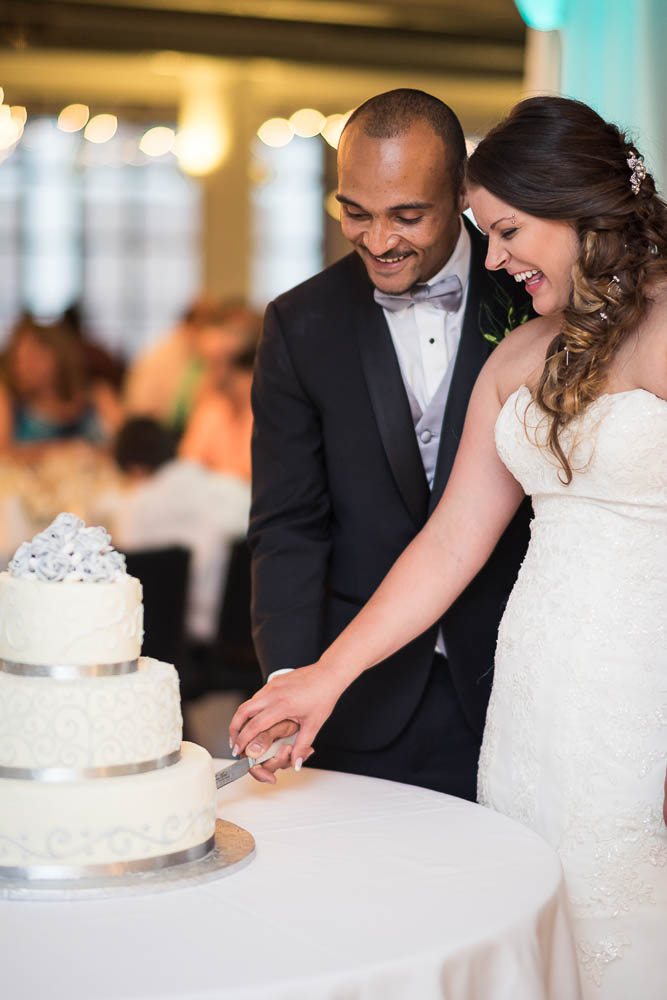 A bride and groom cut their cake during their summer wedding at Windows on Washington.