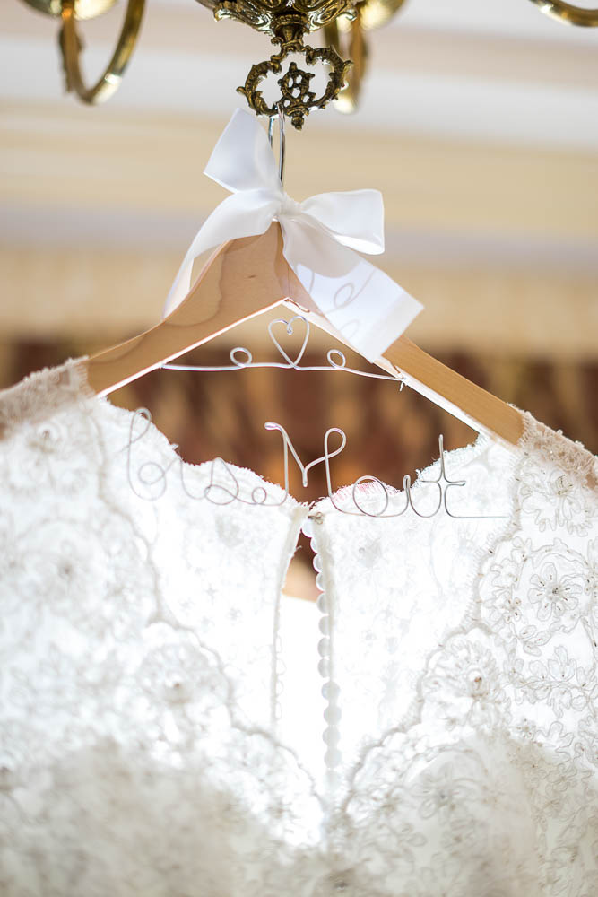 A close up photograph of a brides dress on its hanger.