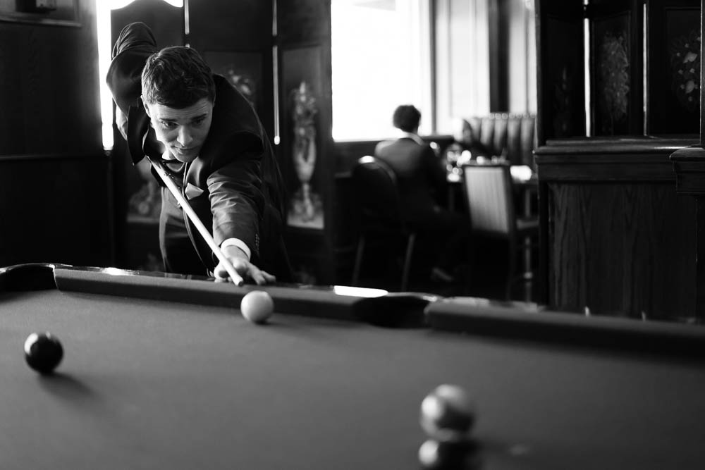 A black and white portrait of a groomsman playing pool before a wedding.