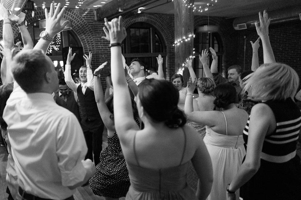 A black and white photograph of wedding guests dancing during a wedding reception at Jim Edmonds Space 15.