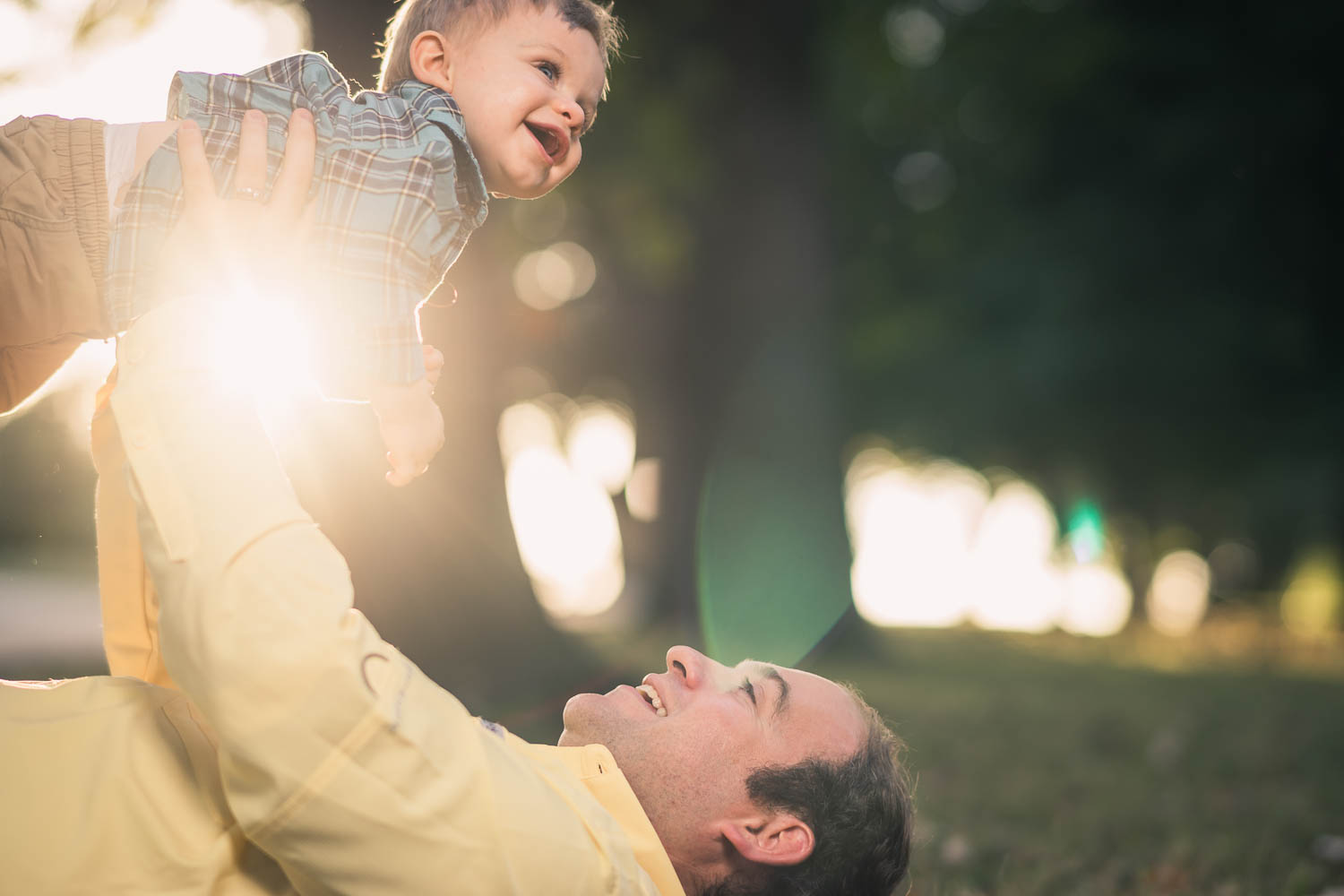 A father lifts his son into the air during a fall family photoshoot in Tower Grove Park.