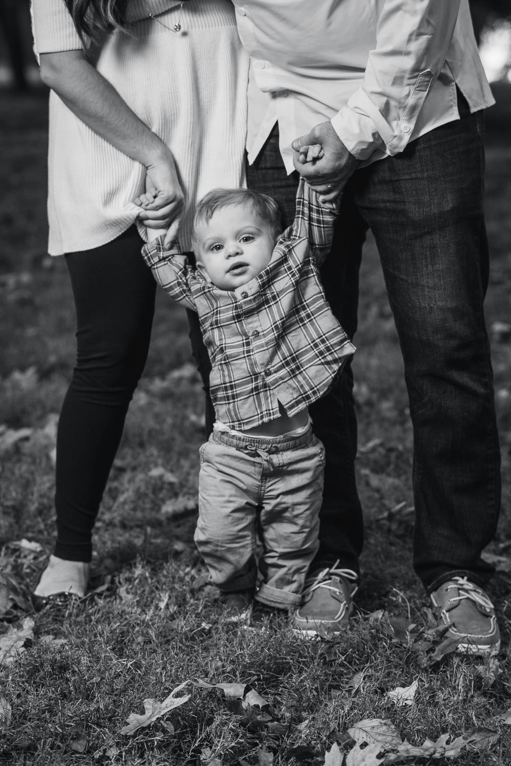 A black and white portrait of a son with his parents during a fall family mini session in Tower Grove Park.