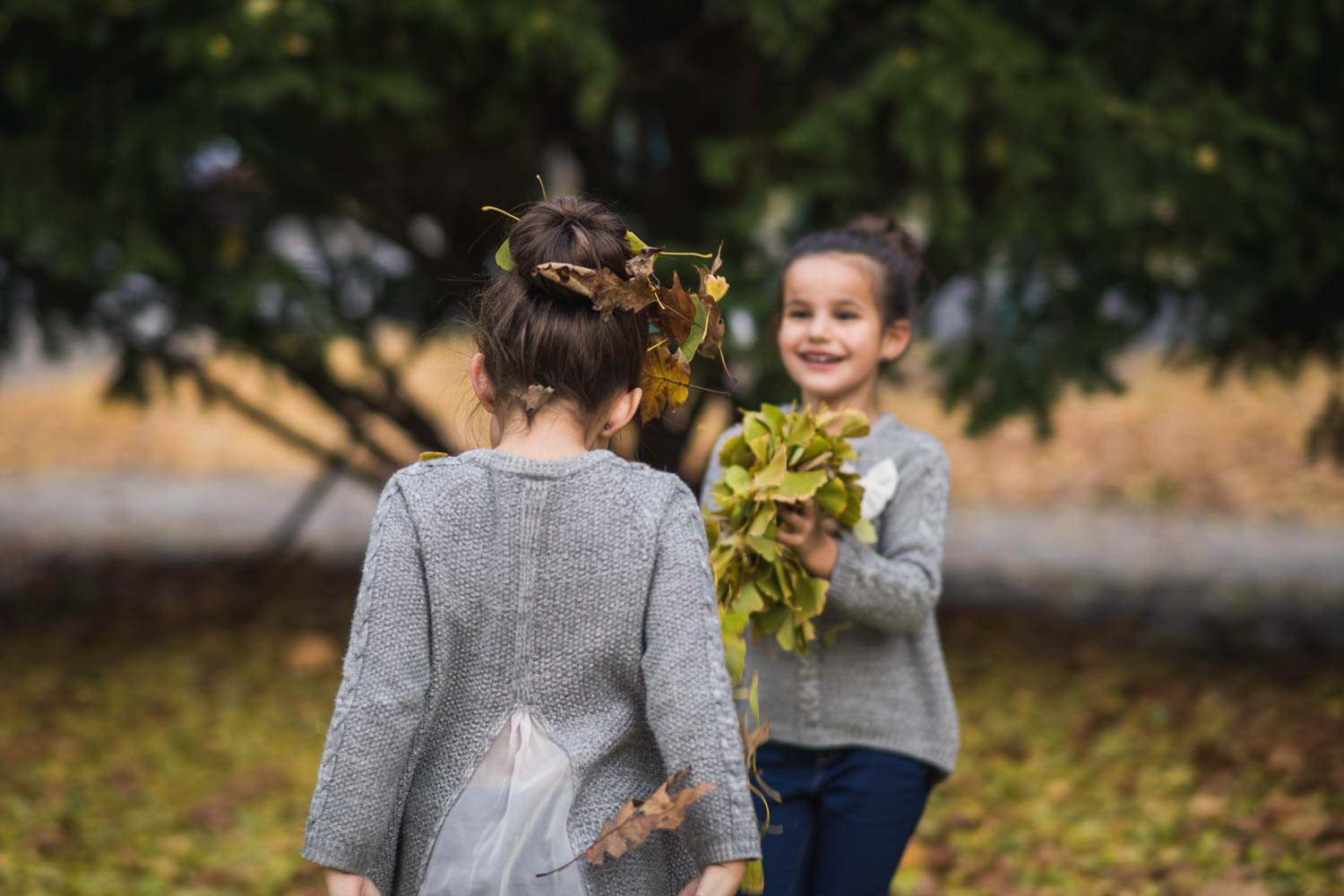 A portrait of kids throwing leaves during their fall family photography mini session at Tower Grove Park.