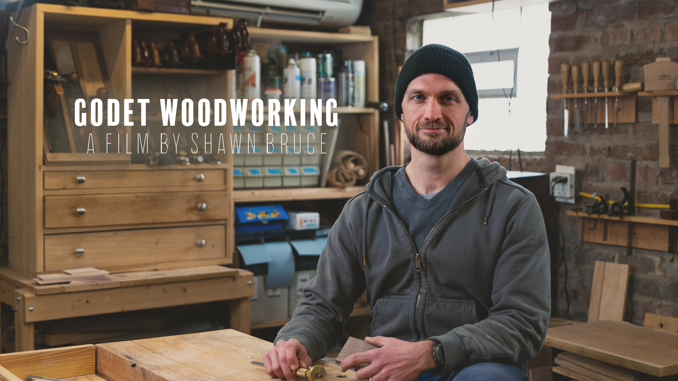 Adam stands in his shop as he explains tools and his process of building furniture.