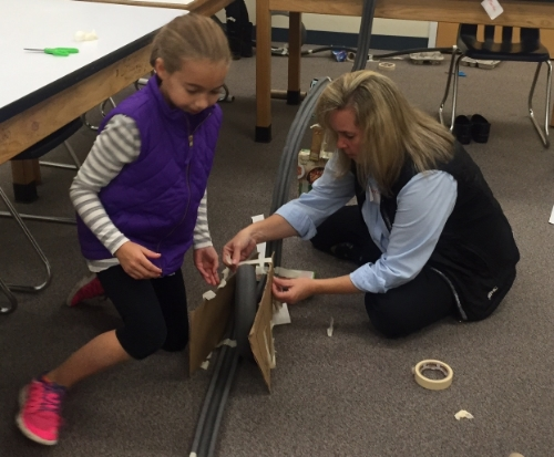 "A mom and daughter work on building a ""marble roller coaster"" in our  Build Bridges!  program"