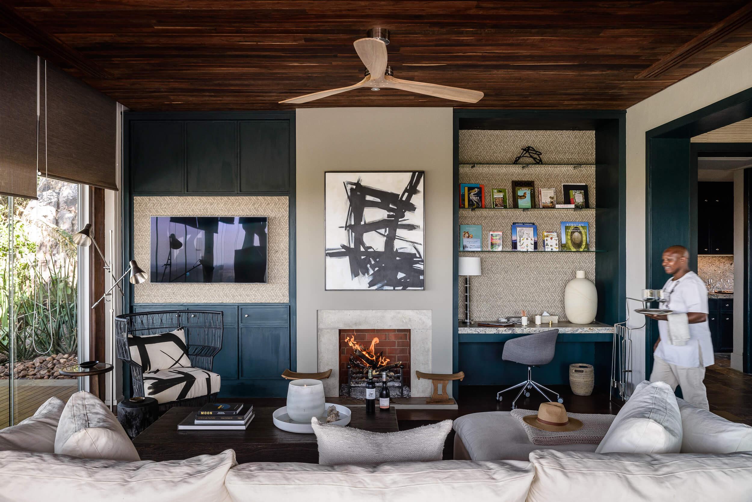Hillside-Suite-Singita-Sasakwa-Lodge-Lounge-Area-with-Fireplace-and-Staff.jpg