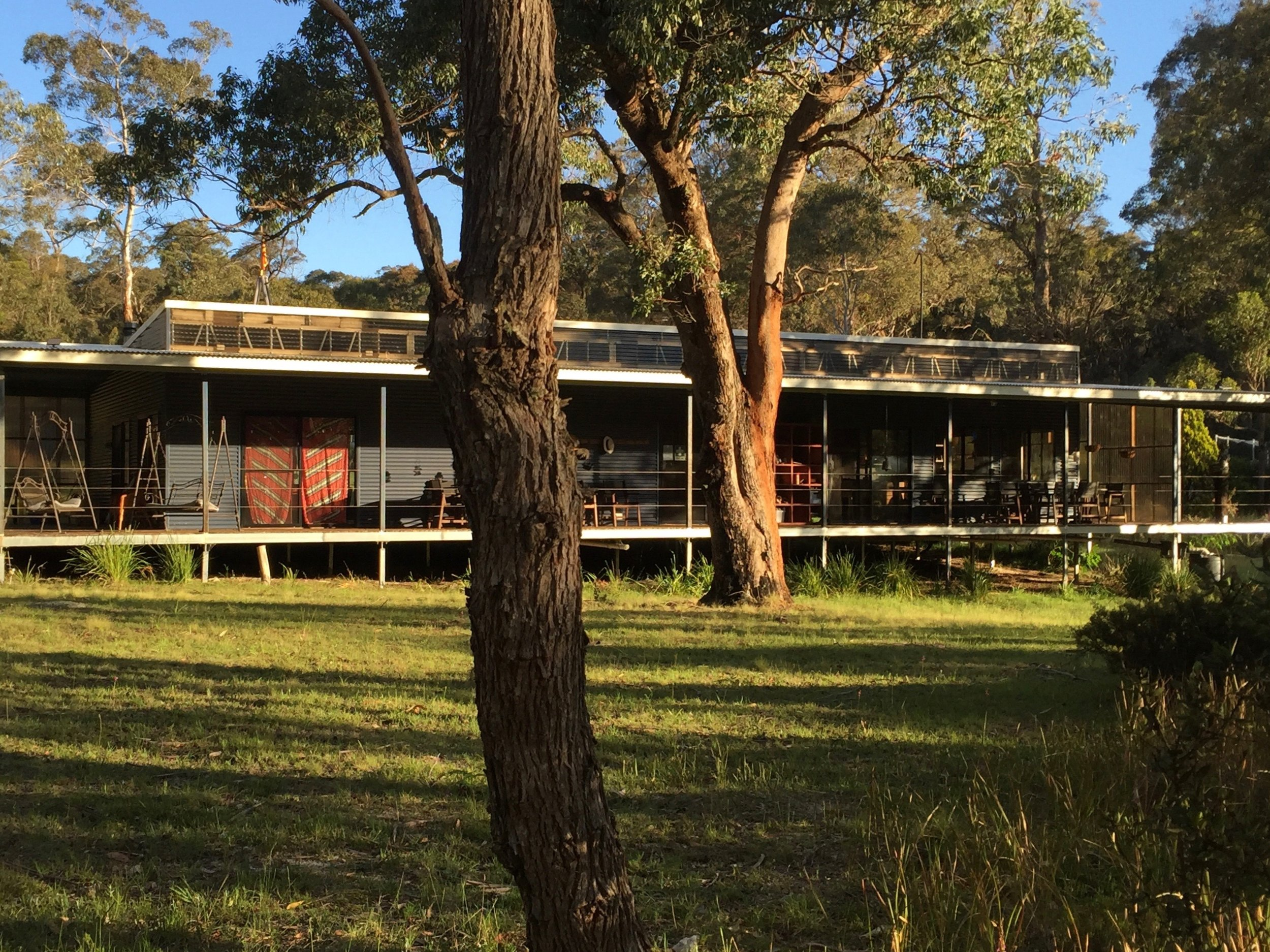 The Ark: once a 12 bay shed, now the hub of the sanctuary after a stylish build and conversion, with a carpeted music and meditation hall, kitchen/dining and a wide verandah for outside dining while the view to the forests.