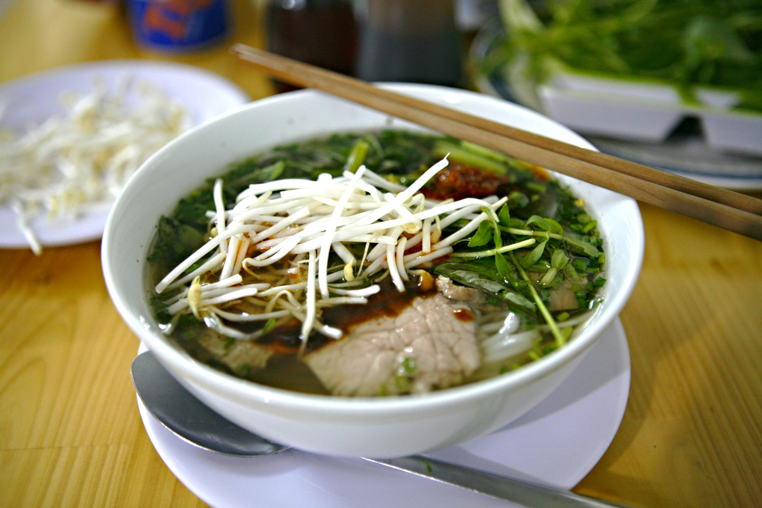 A bowl of piping hot pho bo - garnished with fresh basil, culantro, mung bean sprouts and chili paste