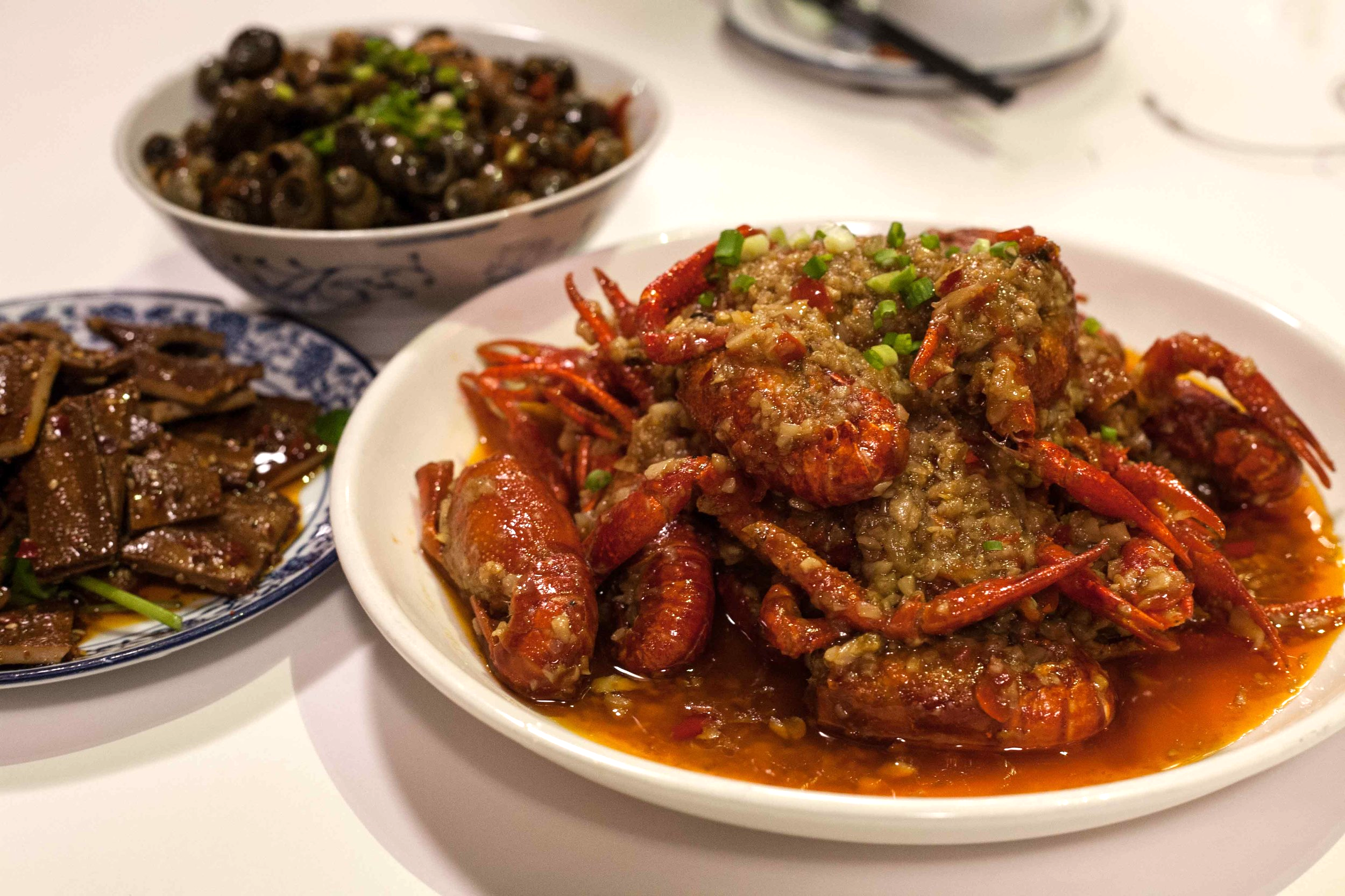 Clockwise from front - Stir-fried whole crawfish with garlic and chili served with smoked bean curd and sea snails