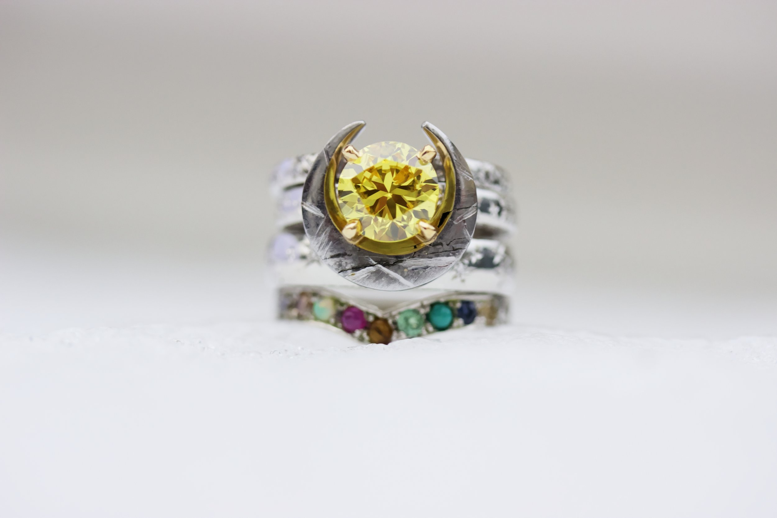 A fiery yellow diamond to represent the Sun, a hand carved Gibeon meteorite brings an element of outer space, and the Pleiades Ring features the 9 planets (including Pluto, thank you very much!)