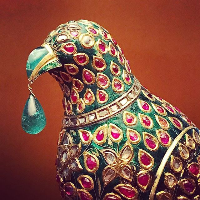 An enamelled and gem set model of a parrot, Hyderabad, Deccan, circa 1775-1825. Set with diamonds, rubies and emeralds and with a pendant emerald hanging from its beak, on a stand similarly decorated, base decorated with two central flowers in green and white enamel and four leaves in each corner courtesy Christie's.  #finejewelry #jewelry #jewellery #antique #antiquejewelry #mughaljewellery #sculpture #heritage #estatejewelry #diamond #jck #lasvegas