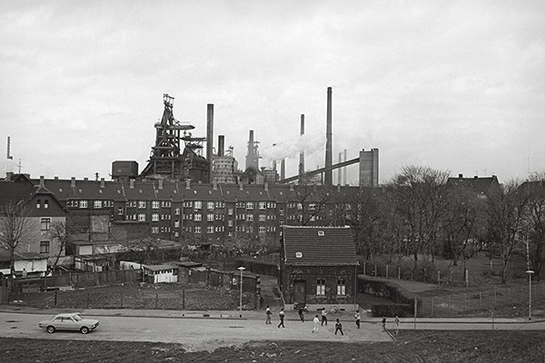 Fußball ist unser Leben. Hier 1985 in Duisburg-Bruckhausen. Vorne das Häuschen, links der Wagen und dahinter die Siedlung. Über allem thronend die Thyssen Hochöfen. Das Ruhrgebiet der Achtziger in einem Bild.