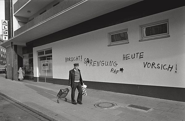 1983 »vorm ALDI«. Ein Sprayer mit Sympathien für die RAF, mit leichter Rechtschreibschwäche. Den einsamen Käufer irritiert das nicht. Er hat noch den Heimweg vor sich. Essen-Frohnhausen ist groß, besonders zu Fuß.
