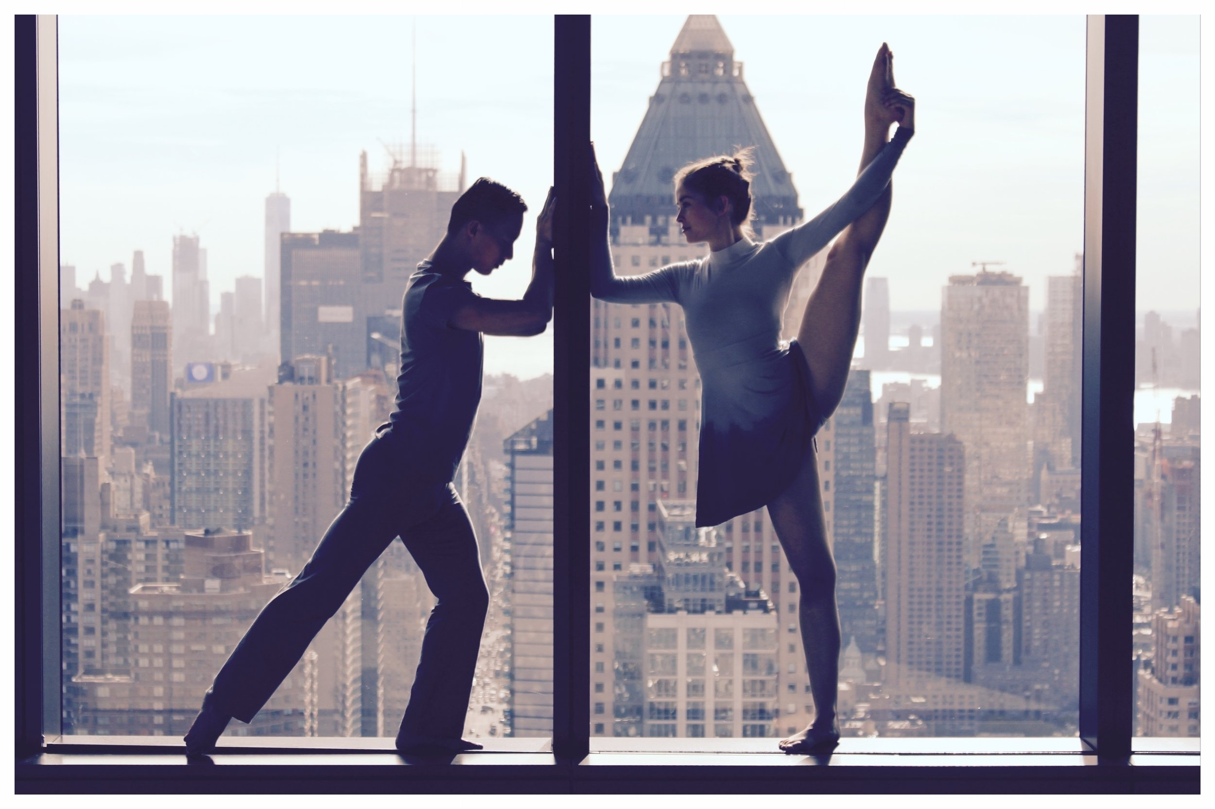 Xiang Xu and Katie Wilson. (Photo: E. M. Whiteley). ( Female and male dancer standing in window on either side of a divide with New York City building behind them.)
